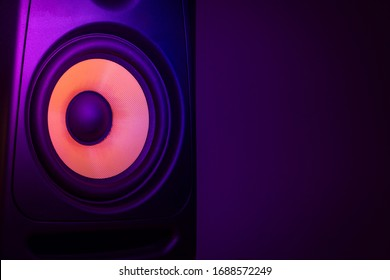 Music studio speaker, with a yellow membrane, isolated on a dark purple background, with space for text on the right side. Electronic music concept.