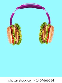 Music tastes so delicious. Pink headphones with burgers as a dynamics against light blue background. Modern art collage. Negative space. Contemporary pop design. Tasty food and juicy sound concept