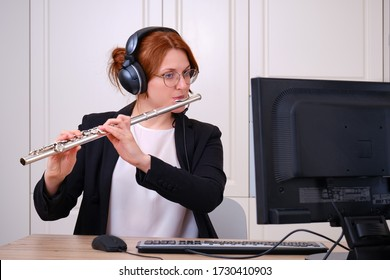A music teacher conducts a lesson on playing a musical instrument over the Internet. Flute lessons online and online music training during quarantine for the coronavirus pandemic