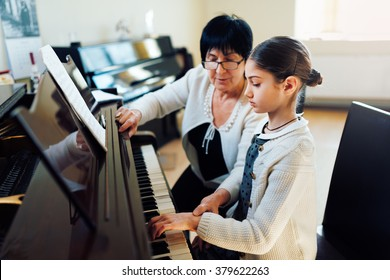 a music teacher with the pupil at the lesson piano