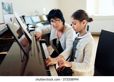 music teacher shows how to play the piano