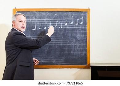 Music teacher writing on a blackboard