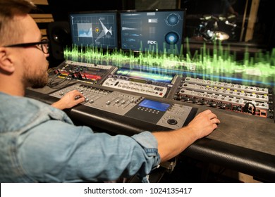music, technology and equipment concept - man at mixing console with computer monitors in sound recording studio
