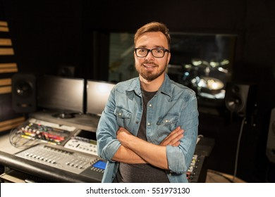 music, technology, people and equipment concept - happy smiling man at mixing console in sound recording studio