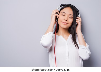 Music waves. Beautiful young Asian in headphones keeping eyes closed and smiling while standing against grey background