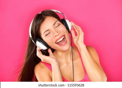 Music. Woman listening to music on headphones enjoying a dance. Closeup portrait of asian girl on pink background