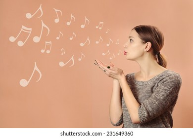 Music for you, Pretty young girl blowing notes