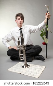 Music. Young man in love with trumpet note sheet red rose on gray background