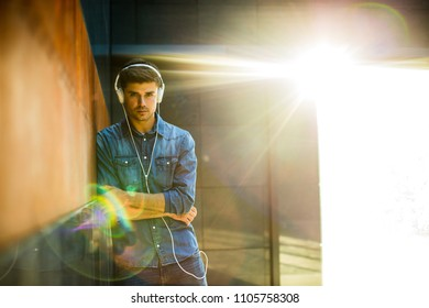 music for youngsters. concept with young guy all in jeans outfit, listening music on headsets in room with flare from the sun
