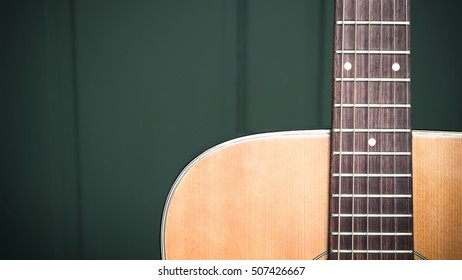 musical background image of acoustic guitar focus on strings with text area, very shallow depth of field. Processed with vintage style.