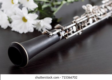 Musical background, poster - oboe on black background with flowers .