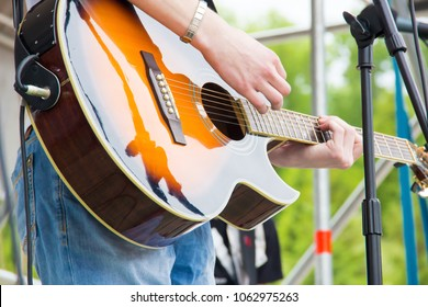 Musical band perfom on an open air festival. Guitarist man playing music by wooden acoustic guitar close-up
