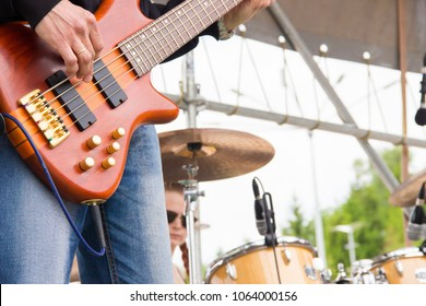 Musical band perfom on an open air festival. Bass guitarist man playing close, drums blurred