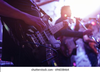 musical band playing concert,guitarist show solo guitar performer with blur singer on the stage,selective focus and light flare effect