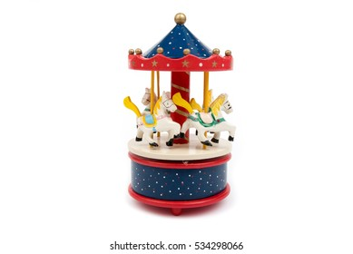 Musical carousel with horses. Blue, red, white merry go round. Toy. Vintage carousel, made from solid wood. Winter, Christmas, New Year decoration. Isolated on white background. Closeup. Front view.