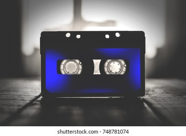 musical cassette black and blue, on a wooden table