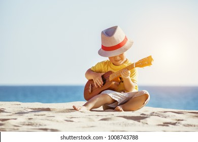 Musical concept with little boy playing ukulele at sunny sea beach