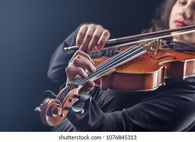 Musical concept. A woman is playing the violin. Focus on the violin