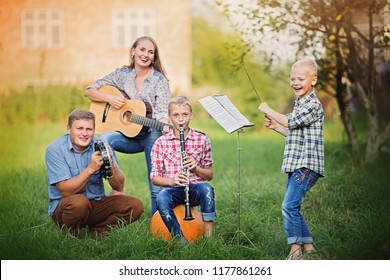 Musical concert. Happy family having fun with musical instruments together outdoors.