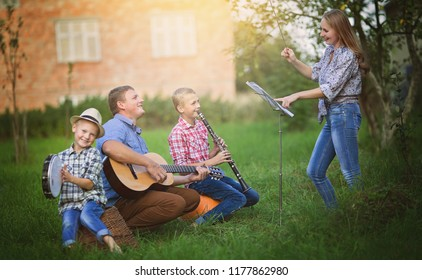 Musical concert. Happy family having fun with musical instruments together outdoors
