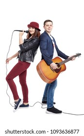 A musical duo of a young couple, a singer in a red hat with a microphone and a handsome guy in a blue jacket with an acoustic guitar. Isolated on white background.