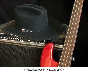 Musical gear ready for a musician to perform in elegant style includes red electric fretless bass guitar, black western hat and amplifier.