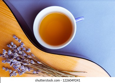 A musical instrument acoustic guitar, yellow wood deck curved shape decorated with dried bunch of lavender flowers and cup of herbal tea, closeup, fragment, top view. concept of music and nature.