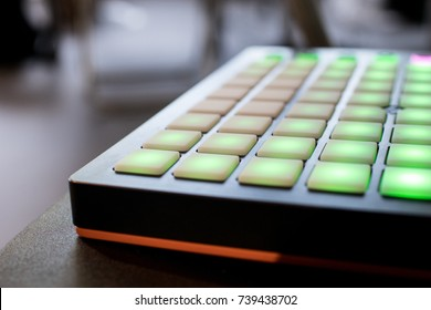 musical instrument for electronic music with a matrix of 64 keys in 8 x 8 files. Pad for music with buttons illuminated by green faded