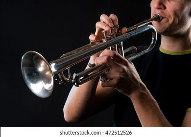 Musical instrument in the foreground with its musician in the black background. Man plays soul on the professional trumpet with great efforts.