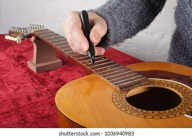 Musical instrument guitar repair and service - Worker preparation of frets for grinding.
