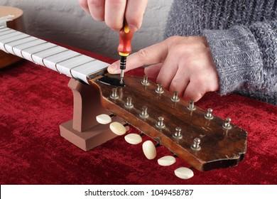 Musical instrument guitar repair and service - Worker regulates a guitar truss rod.