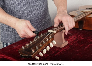 Musical instrument guitar repair and service - Worker fix new strings.