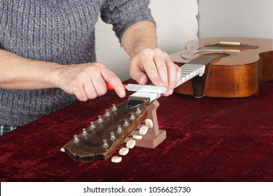 Musical instrument guitar repair and service - Worker to sharpen the special tool guitar neck frets.