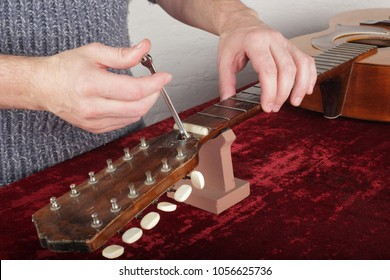 Musical instrument guitar repair and service - Worker make out adjustment of an truss rod neck.