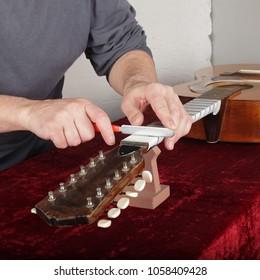 Musical instrument guitar repair and service - Worker sharpen special tool bridge servo nut.
