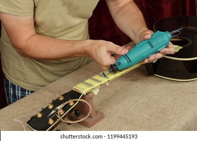 Musical instrument guitar repair and service - Worker polishing guitar neck frets dremel and paste GOI.