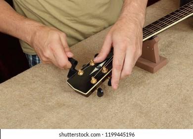 Musical instrument guitar repair and service - Worker fix new strings black acoustic guitar