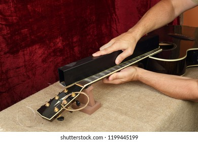 Musical instrument guitar repair and service - Worker grinds black acoustic guitar neck frets.
