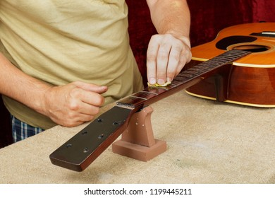 Musical instrument guitar repair and service - Worker moistening and impregnation of an fingerboard neck special oil.