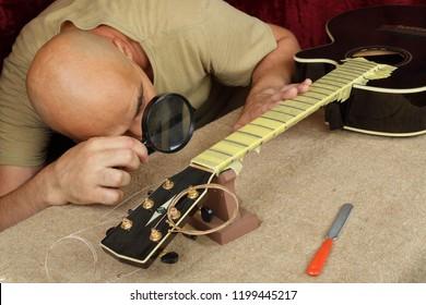 Musical instrument guitar repair and service - Worker control sharpen special tool bridge servo nut black acoustic guitar
