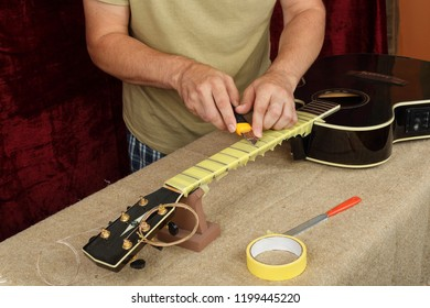 Musical instrument guitar repair and service - Worker preparation pasting of frets for grinding black acoustic guitar