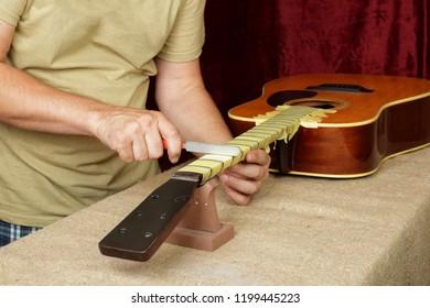 Musical instrument guitar repair and service - Worker sharpen special tool bridge servo nut nat acoustic guitar