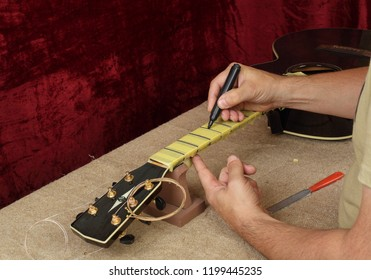 Musical instrument guitar repair and service - Worker preparation of frets for grinding black acoustic guitar