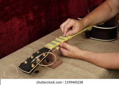 Musical instrument guitar repair and service - Worker polishing guitar neck frets Sandpaper