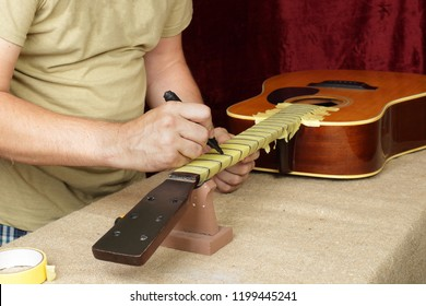 Musical instrument guitar repair and service - Worker preparation of frets for grinding acoustic guitar