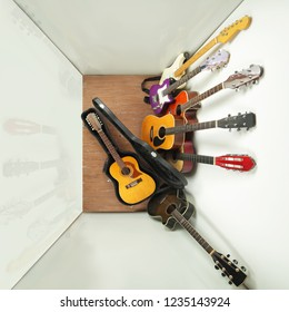 Musical instrument - lot of hard case, acoustic guitars on a white and wood background.
