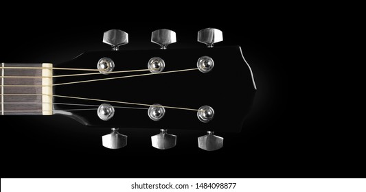 Musical instrument - headstock peghead black acoustic guitar isolated on a black background.