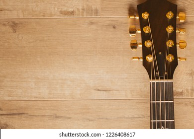 Musical instrument - Neck acoustic guitar on a wooden background. Guitar Head Stock on wooden table with copy space. 8-string Acoustic-electric Baritone Guitar.