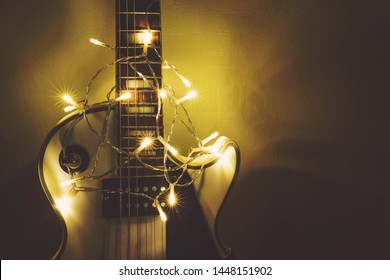 Musical instrument on dark background. Electric guitar with lighted garland on dark background. Gift guitar classic shapes for Christmas or new year.