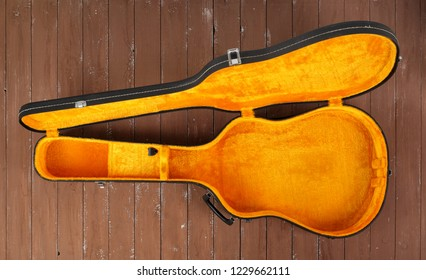 Musical instrument - Open black and yellow acoustic guitar hard case on a wooden background